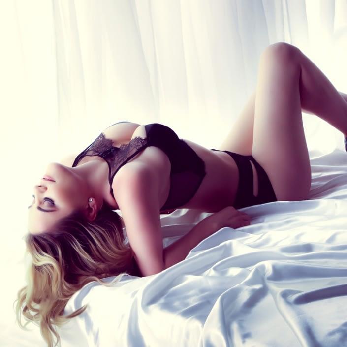 orange county boudoir studio woman laying bed wearing victoria secret